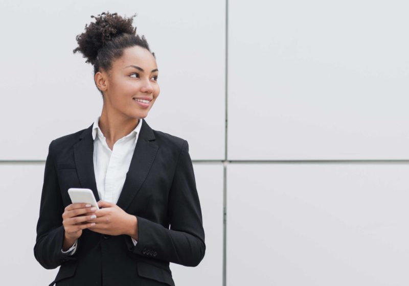BSc finance and accounting female student smiling and holding a cell phone