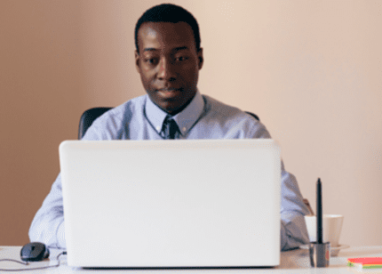 MBA in General male student working on laptop